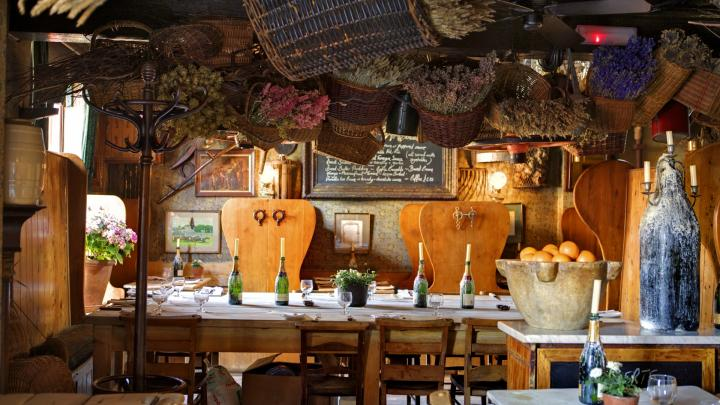 Farmhouse-style British menu in a restaurant themed like an old barn, including baskets and beehive.